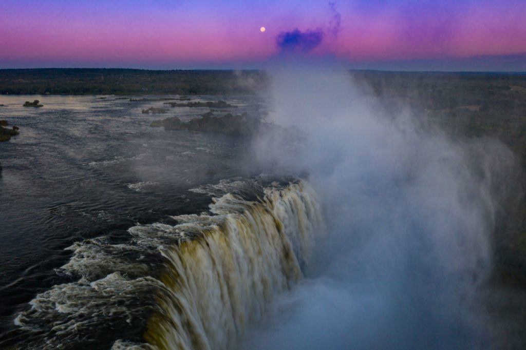 The moon rises above the Victoria Falls on May 7
